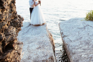 beautiful gorgeous blonde bride and stylish groom on rocks, on the background of a sea